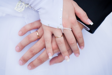 Wedding details - closeup of hands of newly-married with gold rings photo
