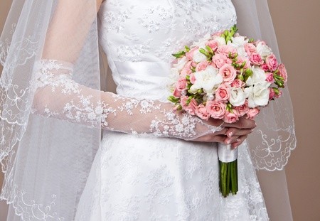 Bride holding a beautiful wedding bouquet of flowers photo