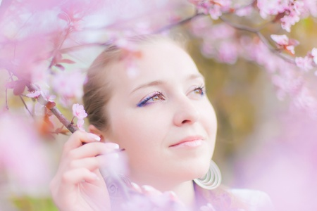 beautiful girl in the flowers of the apricot tree Stock Photo