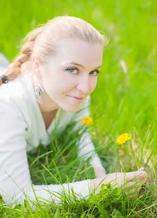 girl on yellow dandelion on green field photo
