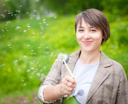 beautiful Girl with dandelion on green field photo