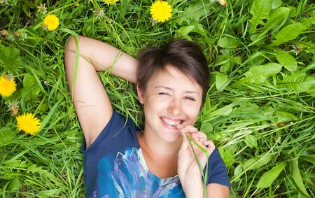 girl on dandelion on green spring field photo