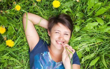 girl on dandelion on green spring field photo
