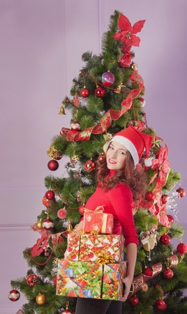 Girl with gift boxes near christmas tree photo