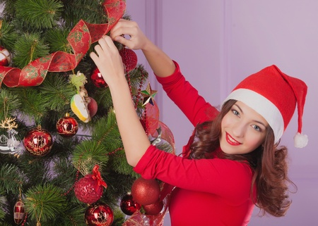 A young girl decorates the Christmas tree Stock Photo - 17008840
