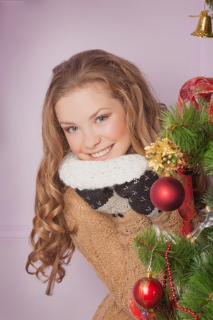 Attractive brunette in red Santa's cap looking out of Christmas tree Stock Photo - 17008865