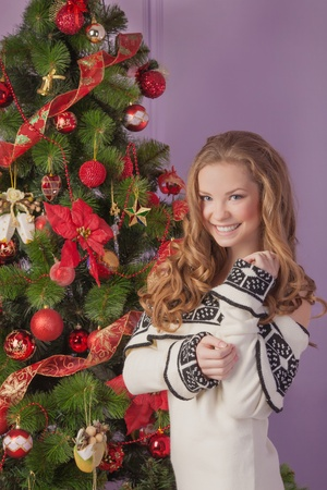 A young girl decorates the Christmas tree Stock Photo - 17008815