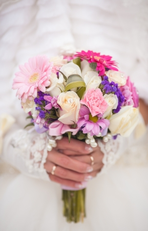 Beautiful wedding bouquet in hands of the bride photo