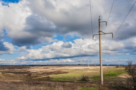 Electrical net of poles on a panorama of blue sky and green meadow photo