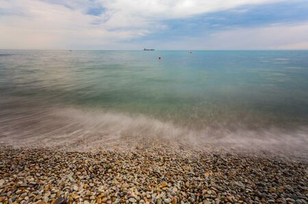 pebble stones by the sea. Silky waves of blue sea from long exposure. photo
