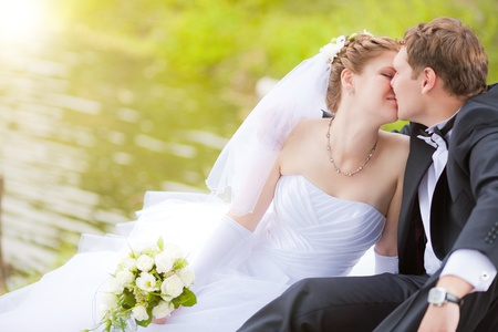 the newly married couple kissing in park