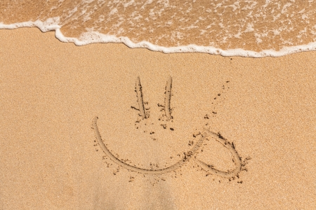 Sun Hollidays Written in the Sand on a Beach with Drawing of the Sun and Sea in Background photo