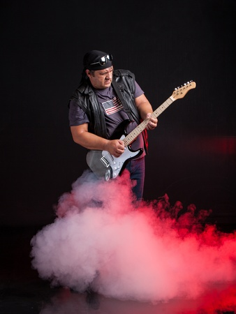 old school rock musician is playing electrical guitar  Shot in a studio  photo