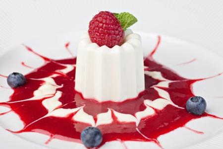 panacotta dessert with ripe raspberries, sprinkled syrup photo