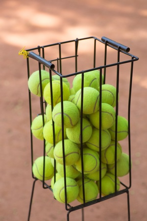 Basket with tennis balls on a court photo
