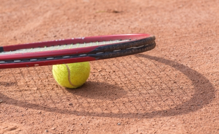 Close up view of tennis racket and balls on the clay tennis court photo