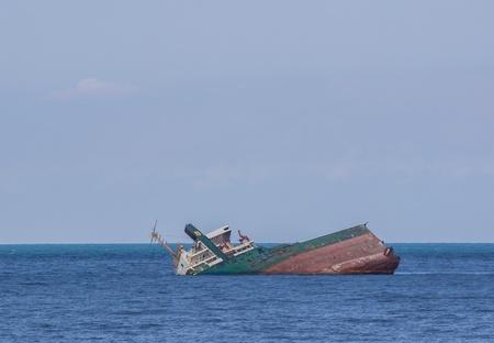 sunk: Sunk ship in blue water, aground, near the coast. Stock Photo