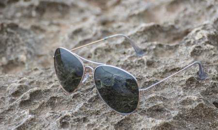 Pair Of Aviator Sunglasses Lying On The Beach photo