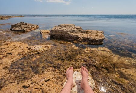 man sitting on the rocks near the ocean photo