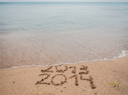 New Year 2014 is coming concept - inscription 2013 and 2014 on a beach sand, the wave is starting to cover the digits 2013 photo