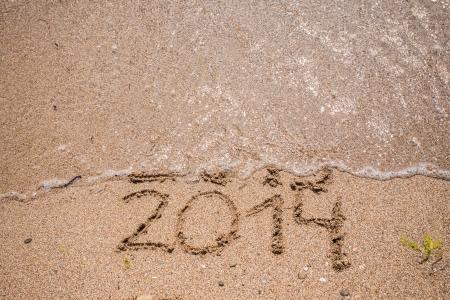 A�o nuevo 2014 viene concepto - inscripci�n 2013 y 2014 en una playa de arena, la ola est� empezando a cubrir los d�gitos 2013 photo