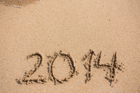 twenty thirteen: New Year 2014 is coming concept - inscription 2013 and 2014 on a beach sand, the wave is starting to cover the digits 2013