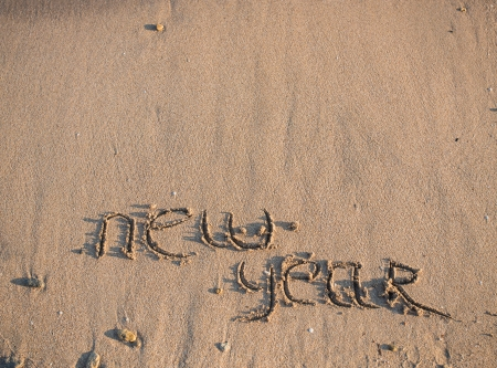 New Year 2014 is coming concept - inscription 2013 and 2014 on a beach sand, the wave is starting to cover the digits 2013 Stock Photo - 23722134