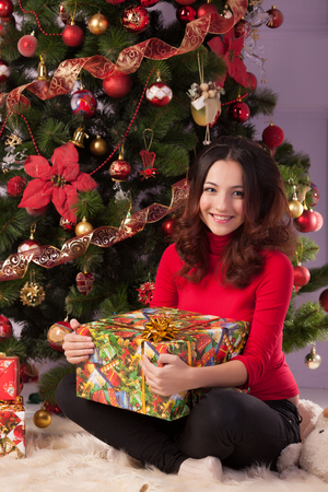 Beautiful girl with a gift near the Christmas tree photo