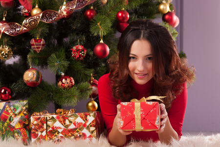 woman hanging toy: Beautiful girl with a gift near the Christmas tree