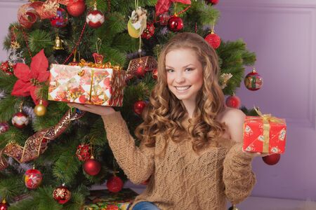 Beautiful girl with a gift near the Christmas tree Stock Photo - 23667162