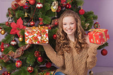 Beautiful girl with a gift near the Christmas tree Stock Photo - 23667163