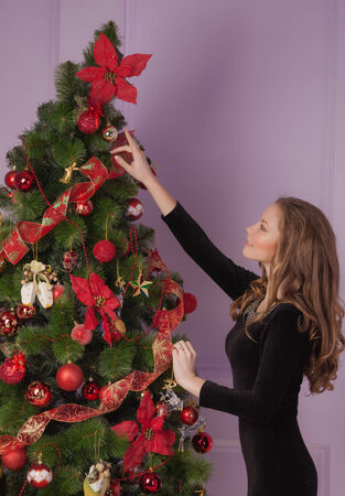 Beautiful girl hanging toy on Christmas tree photo
