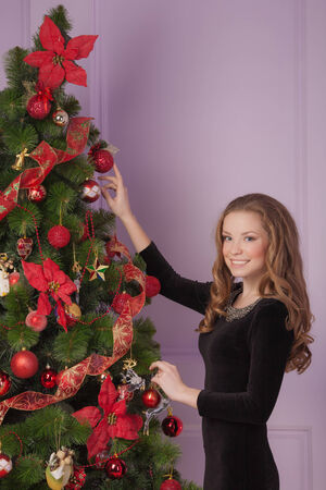 Beautiful girl hanging toy on Christmas tree Stock Photo - 23665915