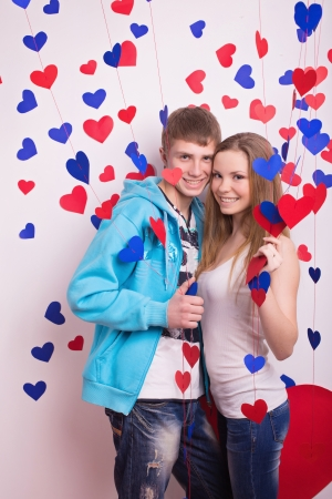 Beautiful young smiling couple in love embracing indoor photo
