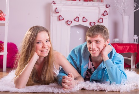 Beautiful young smiling couple in love embracing indoor Stock Photo - 25894238