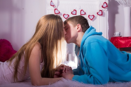 Beautiful young kissing couple in love embracing indoor photo