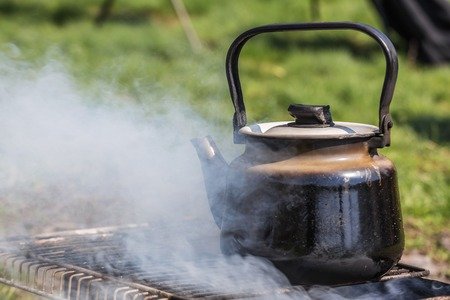 Kettle boiling over gas burner on the nature photo