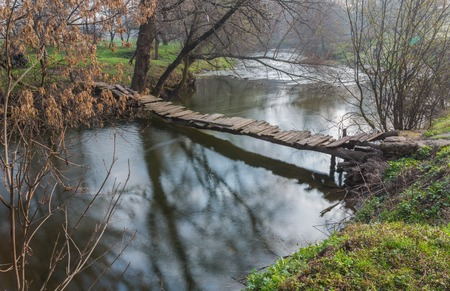 landscape with a wooden bridge over the river Stock Photo