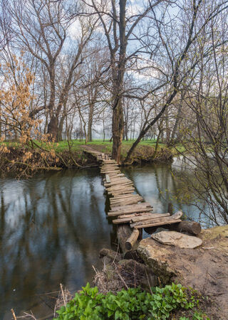 landscape with a wooden bridge over the river photo
