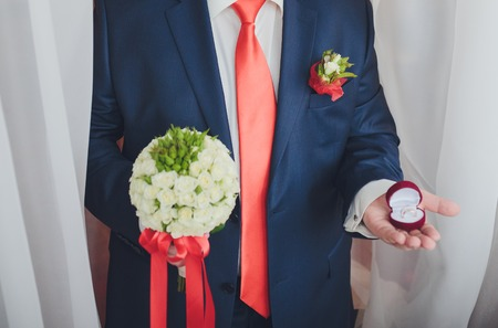 Engagement ring or present in the hands of a man in suit photo