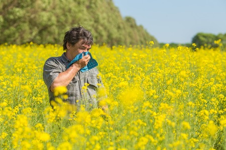man in field blowing his nose and suffering from hay fever. photo