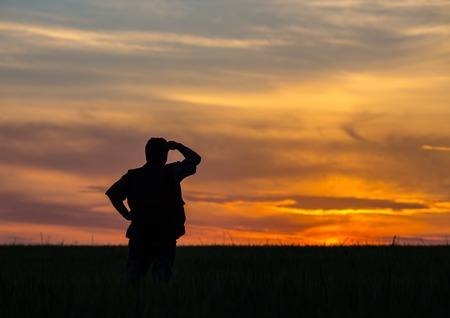 silhouette of man standing in a field at sunset photo