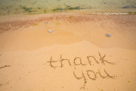 Thank you written in the sand on the beach. photo