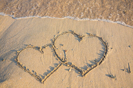 couple drawing a heart on wet golden beach sand photo