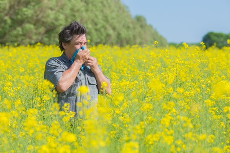 hayfever: man in field blowing his nose and suffering from hay fever. Stock Photo