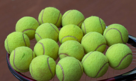 avocation: Close up view of tennis racket and balls on the clay tennis court