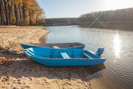yellow boats: Two boats on the lake, pond. Yellow leaves of the trees.