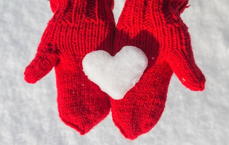 winter fashion: snowflake in the form of heart on red mittens