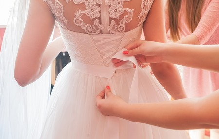 beautiful dress: Helping the bride to put her wedding dress on Stock Photo