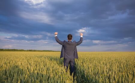 thumb: happy farmer, businessman, standing in wheat field over wind turbines background with his hands up and thumbs up Stock Photo